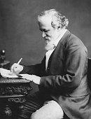 English poet Robert Browning writng at a desk circa 1880