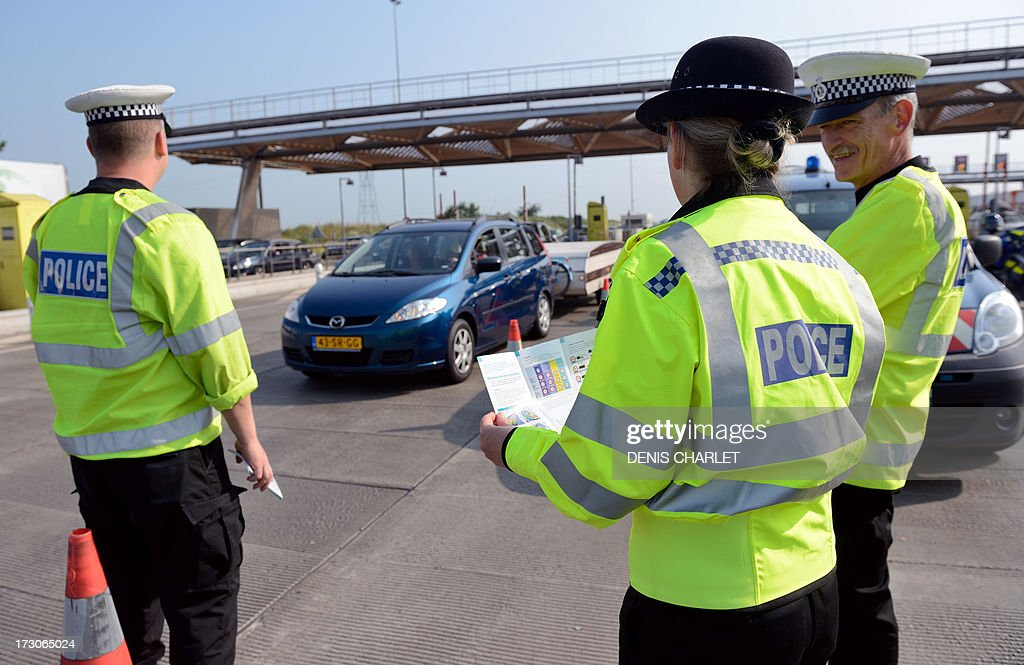 English police officers check vehicles at a toll station in Fresnes-les-Montauban, near Arras northern France, on July 6, 2013, working in collaboration with Belgian, Dutch and French police officers during the first wave of departures for the summer holiday.