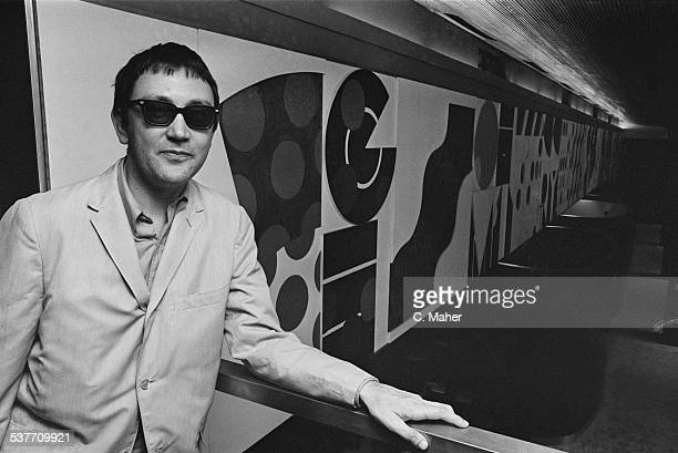 English pop art painter sculptor and printmaker Joe Tilson posing next to his mural 1966