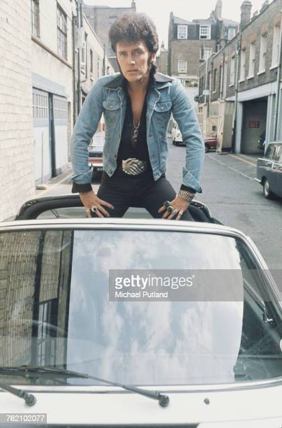 English pop singer Alvin Stardust posed wearing a denim jacket and large buckle belt sitting in the rear of an open topped sports car in a mews...