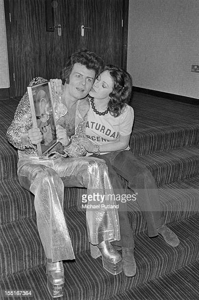 English pop singer Gary Glitter receives a kiss from a fan 12th March 1974 He is holding an award for sales of his single 'I Love You Love Me Love'