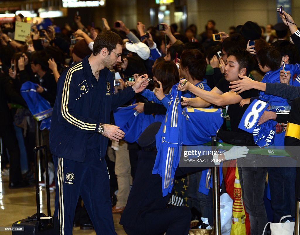 English Premier League football team Chelsea FC goalkeeper Petr Cech (C) signs autographs for Japanese fans upon the team's arrival at Narita International Airport in Narita, suburban Tokyo on December 9, 2012. Chelsea will play a semi-final match in the Club World Cup tournament in Yokohama on December 13. AFP PHOTO / Yoshikazu TSUNO