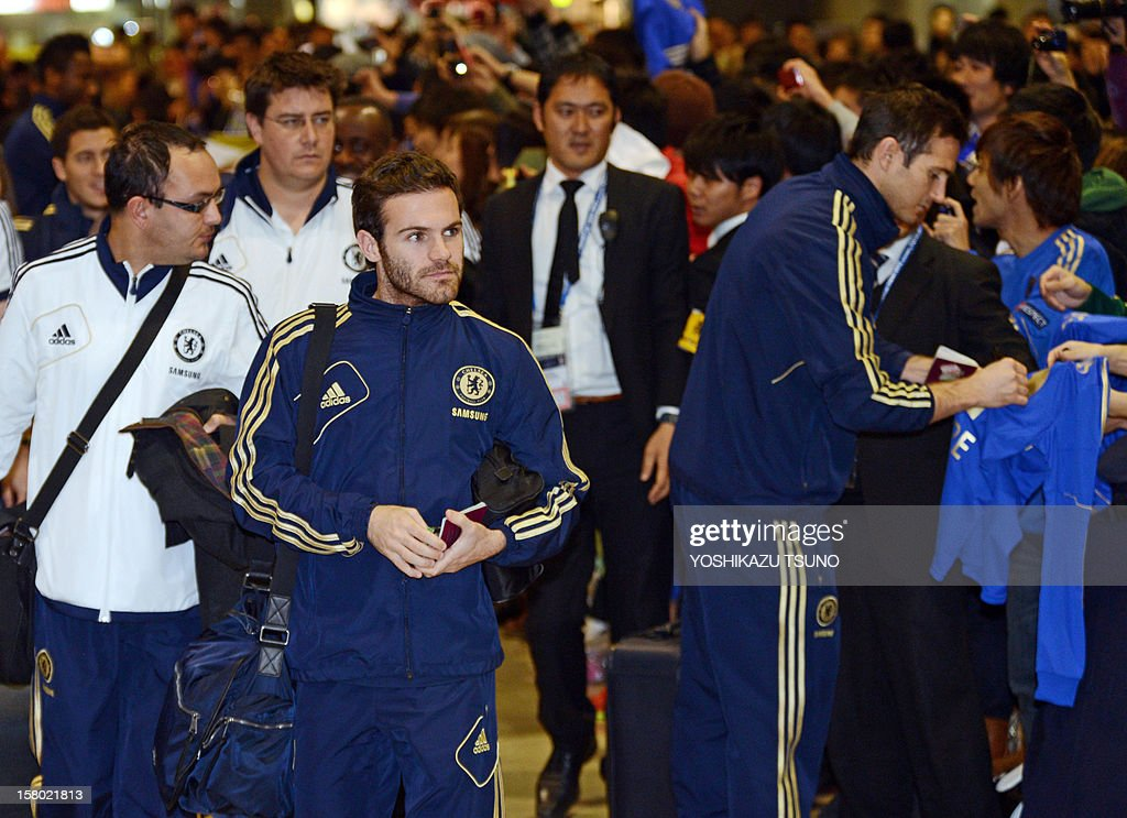 English Premier League football team Chelsea midfielder Juan Mata (L) arrives while teammate Frank Lampard (R) gives autographs for Japanese fans upon their arrival at Narita International Airport in Narita, suburban Tokyo on December 9, 2012. Chelsea will play a semi-final match in the Club World Cup tournament in Yokohama on December 13. AFP PHOTO / Yoshikazu TSUNO