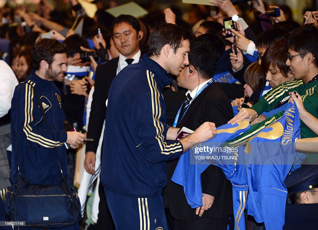 English Premier League football team Chelsea midfielders Frank Lampard (C) and Juan Mata (L) sign autographs for Japanese fans upon their arrival at Narita International Airport in Narita, suburban Tokyo on December 9, 2012. Chelsea will play a semi-final match in the Club World Cup tournament in Yokohama on December 13. AFP PHOTO / Yoshikazu TSUNO