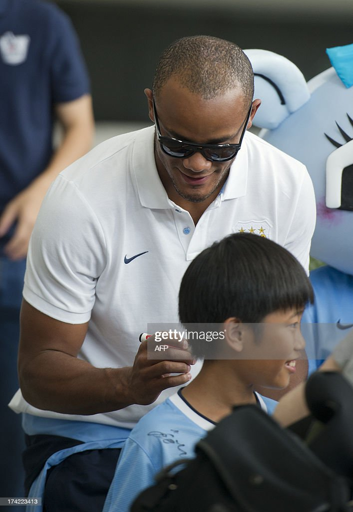 English Premier League football team Manchester City captain Vincent Kompany (top) signs a young fan's shirt in Hong Kong on July 22, 2013. Manchester City will be playing local team South China on July 24.