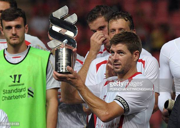 English Premier League Liverpool football player Steven Gerrard holds up the trophy following victory over Thailand at Rajamangala National Stadium...