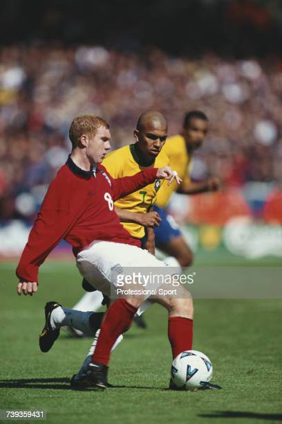 English professional footballer and midfielder with England Paul Scholes pictured with the ball as Marcio Amoroso of Brazil moves in during the...