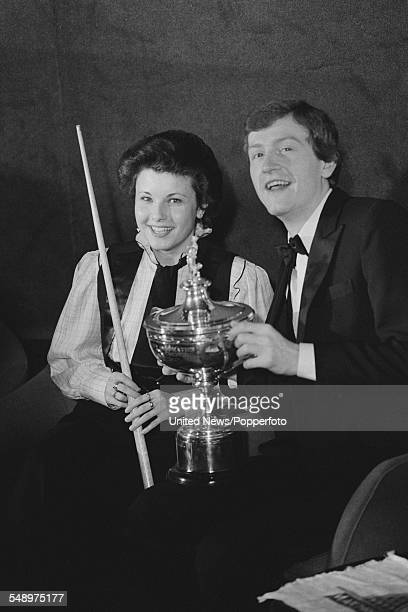 English professional snooker player Steve Davis pictured holding the World Snooker Championship trophy with female snooker player Mandy Fisher on 4th...