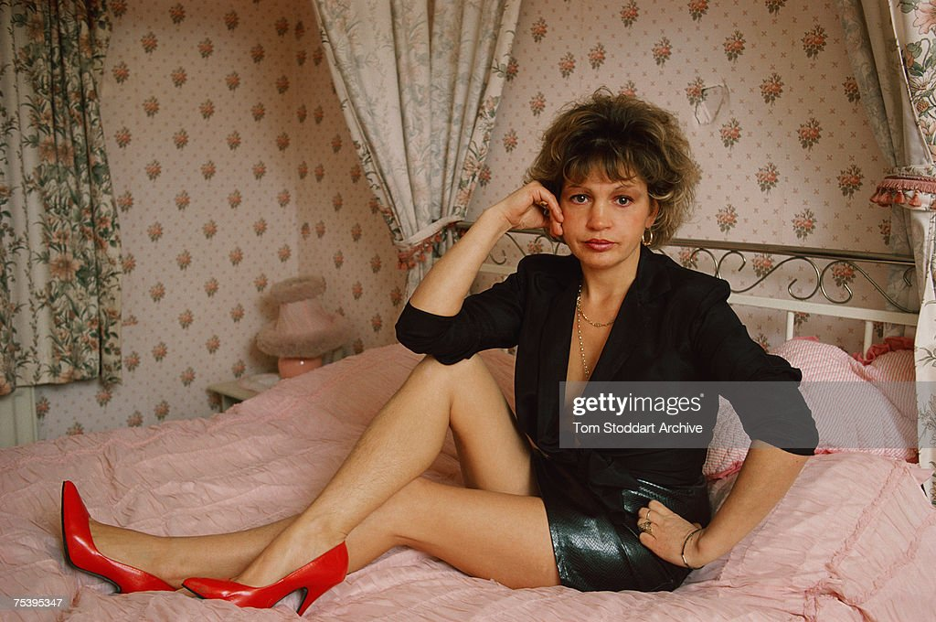 English prostitute Monica Coghlan (1951 - 2001) on the four-poster bed in her bedroom at home in Rochdale, January 1987. In 1987, English Conservative politician Jeffrey Archer won a libel case against the Daily Star newspaper after it alleged he had slept with Coghlan. It later emerged that he had perjured himself at the trial and this led to Archer's imprisonment in 2001.