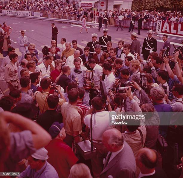 English racing driver Graham Hill driver of the Owen Racing Organisation BRM P57 BRM V8 holds the 21st Automobile Club de Monaco trophy after winning...