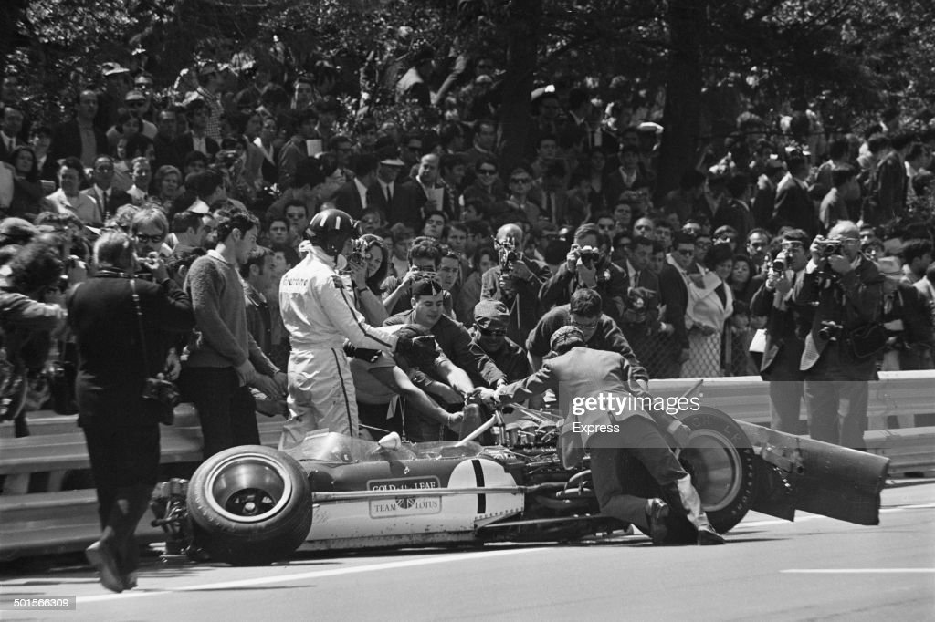 English racing driver Graham Hill with the wreckage of his LotusCosworth 49B after he crashed on the ninth lap of the Spanish Grand Prix at Montjuich...