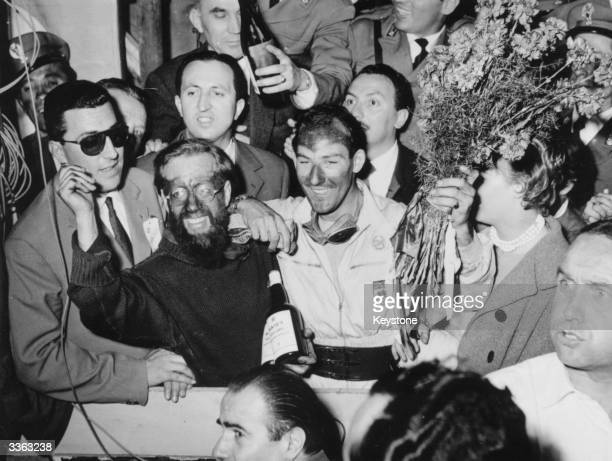 English racing driver Stirling Moss and his partner Jenkinson celebrate after winning the 1955 Mille Miglia race for Mercedes in Italy