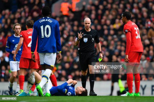 English referee Anthony Taylor prepares to book Everton's English midfielder Ross Barkley for a challenge on Liverpool's Croatian defender Dejan...