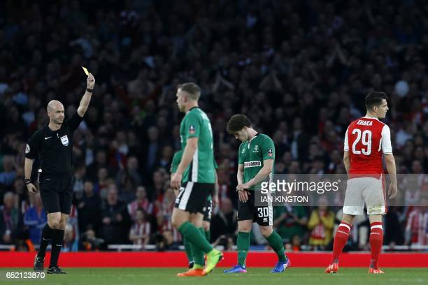 English referee Anthony Taylor shows a yellow card to Arsenal's Swiss midfielder Granit Xhaka during the English FA cup quarter final football match...