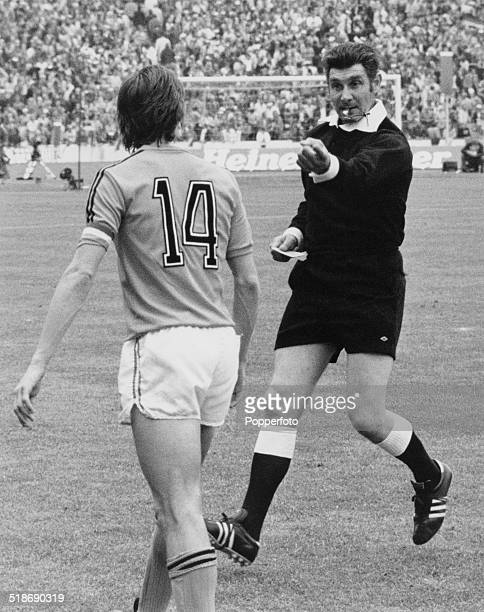 English referee Jack Taylor cautions Netherlands captain Johan Cruyff at the end of the first half of the World Cup final against West Germany at the...