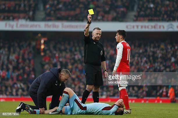 English referee Jonathan Moss books Burnley's prone English midfielder Dean Marney during the English Premier League football match between Arsenal...