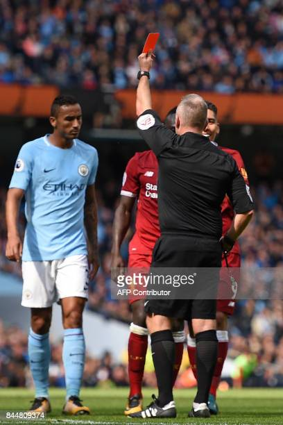 English referee Jonathan Moss shows a red card to Liverpool's Senegalese midfielder Sadio Mane for a dangerous challenge on Manchester City's...