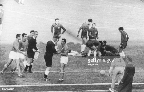 English referee Ken Aston sends off Italian player Mario David while an injured Chilean lies on the ground during the match between Italy and Chile...