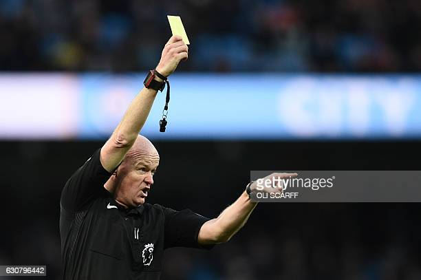 English referee Lee Mason gestures as he shows a yellow card to Manchester City's Ivorian midfielder Yaya Toure during the English Premier League...