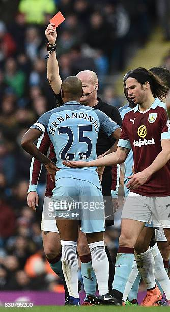 English referee Lee Mason shows a red card to Manchester City's Brazilian midfielder Fernandinho for his challenge on Burnley's Icelandic midfielder...
