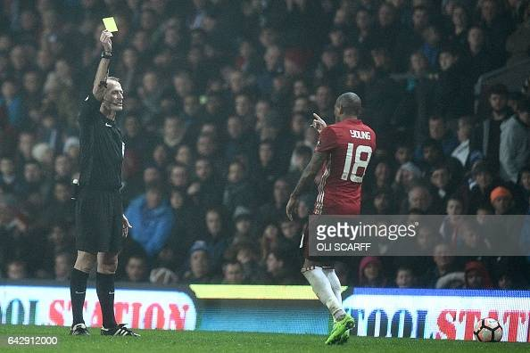 English referee Martin Atkinson shows a yellow card to Manchester United's English midfielder Ashley Young during the English FA Cup fifth round...