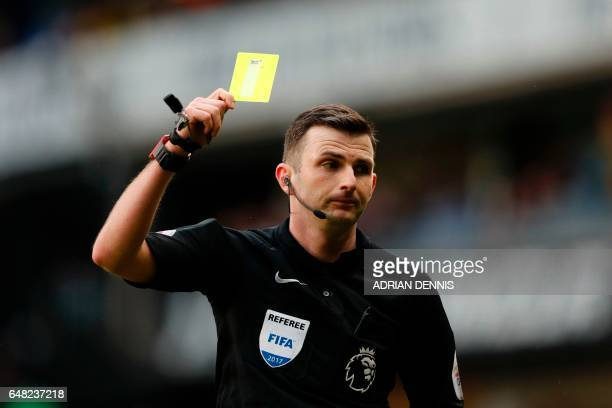 English referee Michael Oliver shows a yellow card during the English Premier League football match between Tottenham Hotspur and Everton at White...