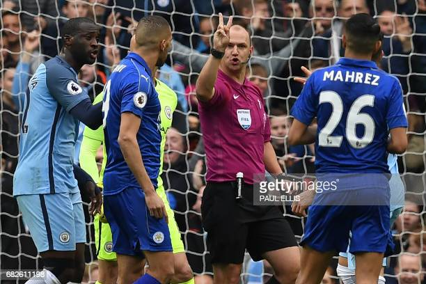 English referee Robert Madley explains to Leicester City's Algerian midfielder Riyad Mahrez that his penalty hit his standing foot on the way to the...