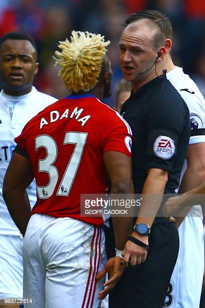 English referee Robert Madley has words with Middlesbrough's Spanish midfielder Adama Traore during the English Premier League football match between...