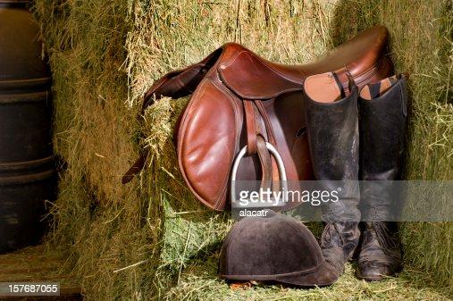 English riding tack on a barn corner next to hay
