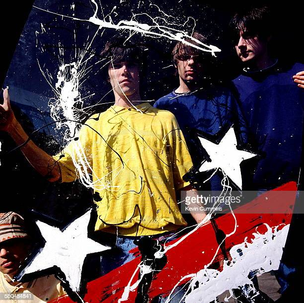 English rock group The Stone Roses holding a painted sheet of clear plastic 8th May 1989 Left to right drummer Alan 'Reni' Wren singer Ian Brown...