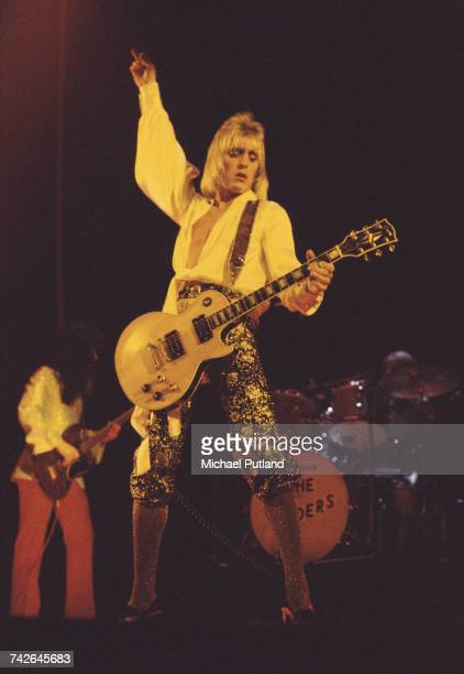 English rock musician and guitarist Mick Ronson of The Spiders from Mars performs live on stage with David Bowie during the Ziggy Stardust/Aladin...