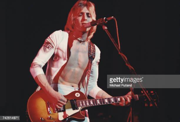 English rock musician and guitarist Mick Ronson performs live on stage playing a Gibson Les Paul guitar with Ian Hunter at the Hammersmith Odeon in...