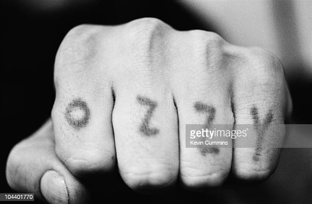 English rock singer Ozzy Osbourne shows off the letters of his name tattooed by himself across the knuckles of his left hand circa 1980