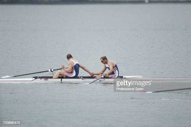 English rowers Matthew Pinsent and Steve Redgrave pictured shaking hands in their boat after finishing in first place for the Great Britain team to...