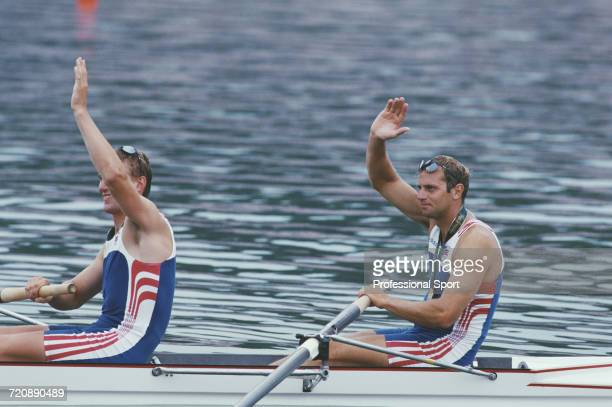 English rowers Matthew Pinsent and Steve Redgrave wave to spectators from their boat after finishing in first place for the Great Britain team to win...