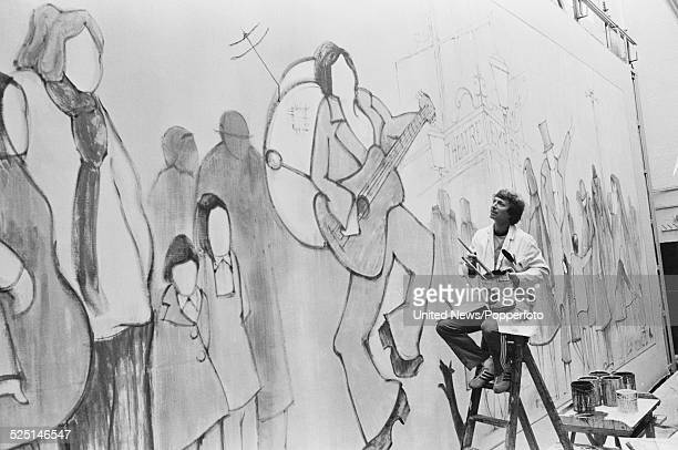 English singer and actor Tommy Steele stands on a ladder to paint a theatre stage set backdrop in London on 26th March 1979