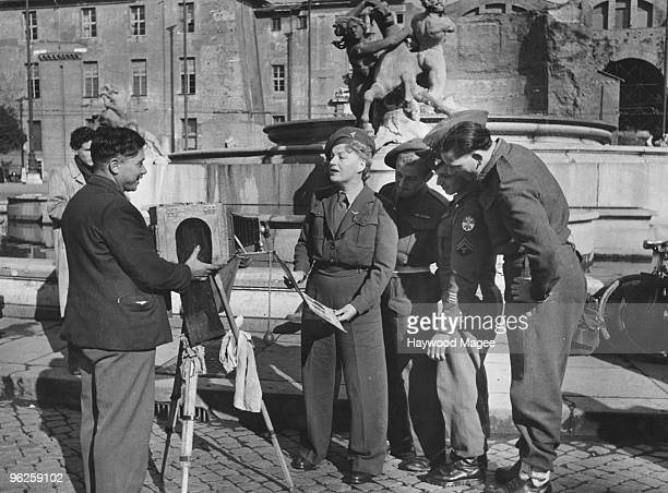 English singer and comedienne Gracie Fields poses for a street photographer with members of the Allied Forces in Rome during an ENSA tour of Italy...