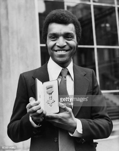 English singer and entertainer Kenny Lynch with his insignia of the Most Excellent Order of the British Empire after the investiture at Buckingham...
