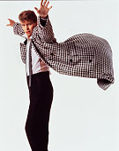 English singer and songwriter David Bowie wearing a houndstooth check coat billowing behind him and pictured at the time of the release of his single...
