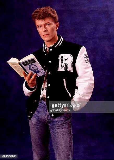English singer and songwriter David Bowie wearing a letterman jacket and holding a copy of the novel 'The Idiot' by Fyodor Dostoyevsky London 1986