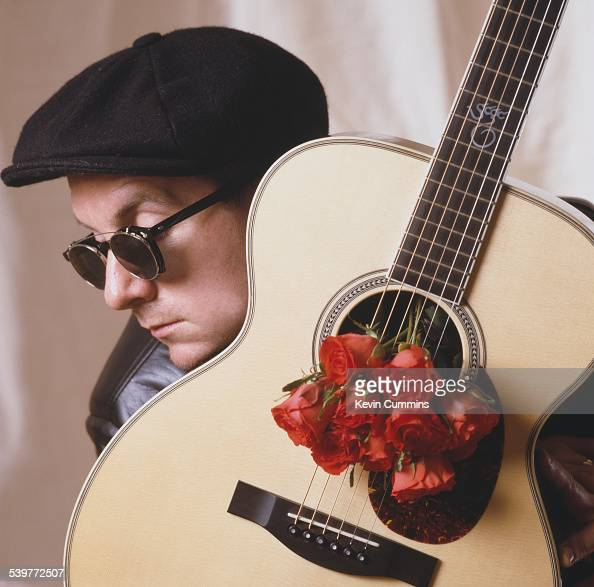 English singer and songwriter Elvis Costello posing with an acoustic guitar decorated with red roses circa 1985
