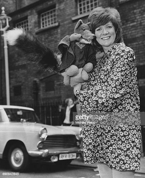 English singer Cilla Black poses with TV's Basil Brush outside the London Palladium where they will both star in the Christmas pantomime 'Aladdin'...