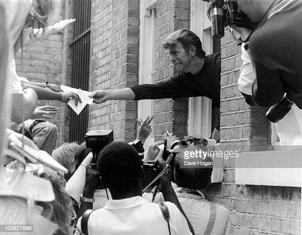 English singer David Bowie leans out of a window to pass autographs to fans during a visit to Brixton London 6th July 1989 Bowie is visiting his...