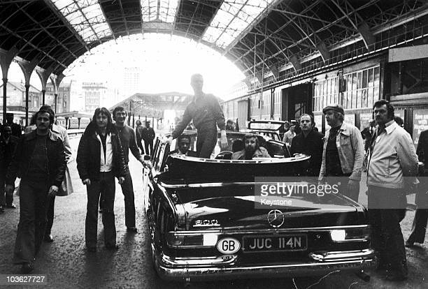 English singer David Bowie standing in a Mercedes convertible at Victoria Station London during his 'Station To Station' tour 2nd May 1976 Moments...