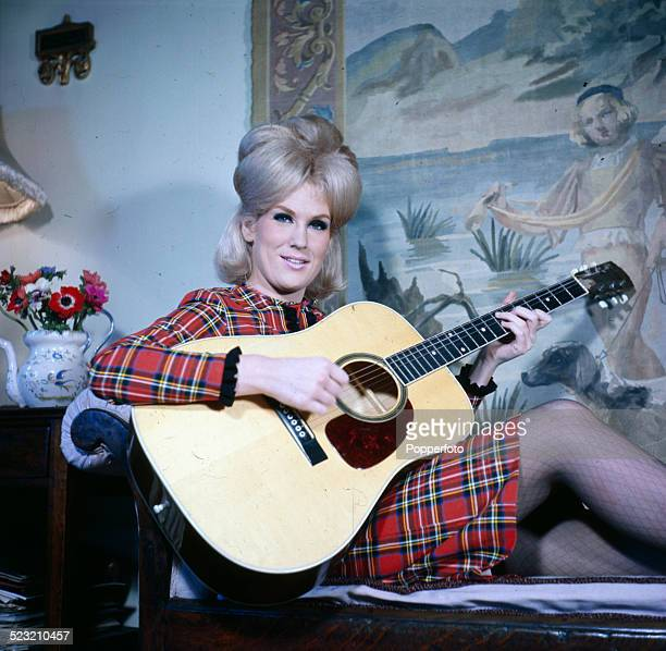 English singer Dusty Springfield pictured wearing a tartan dress whilst playing an acoustic guitar in 1963