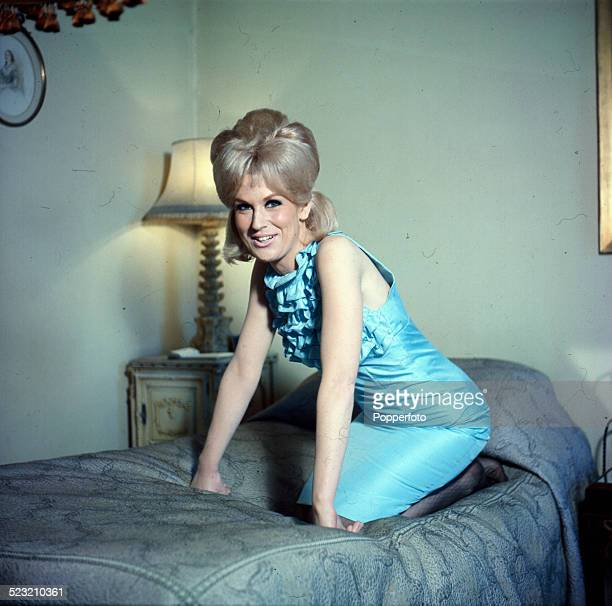 English singer Dusty Springfield posed wearing a light blue dress whilst sitting on a bed in 1963