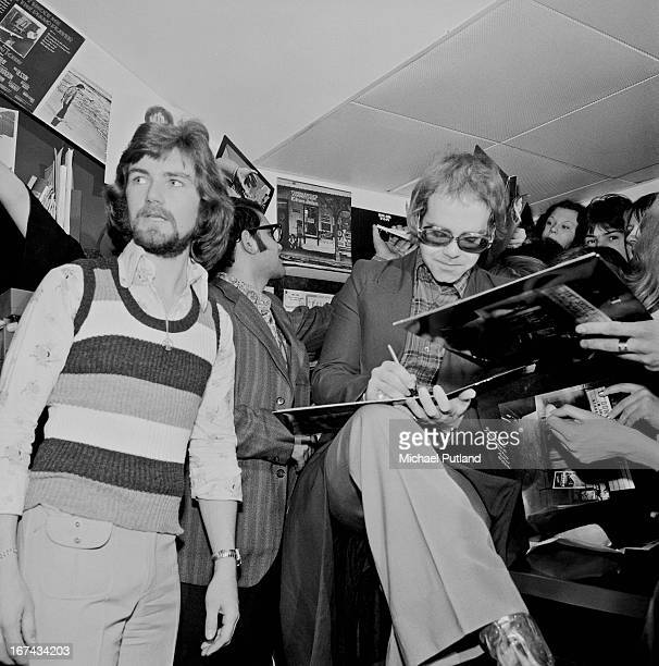 English singer Elton John signing copies of his new album 'Don't Shoot Me I'm Only the Piano Player' at the Record Bar a shop owned by radio...