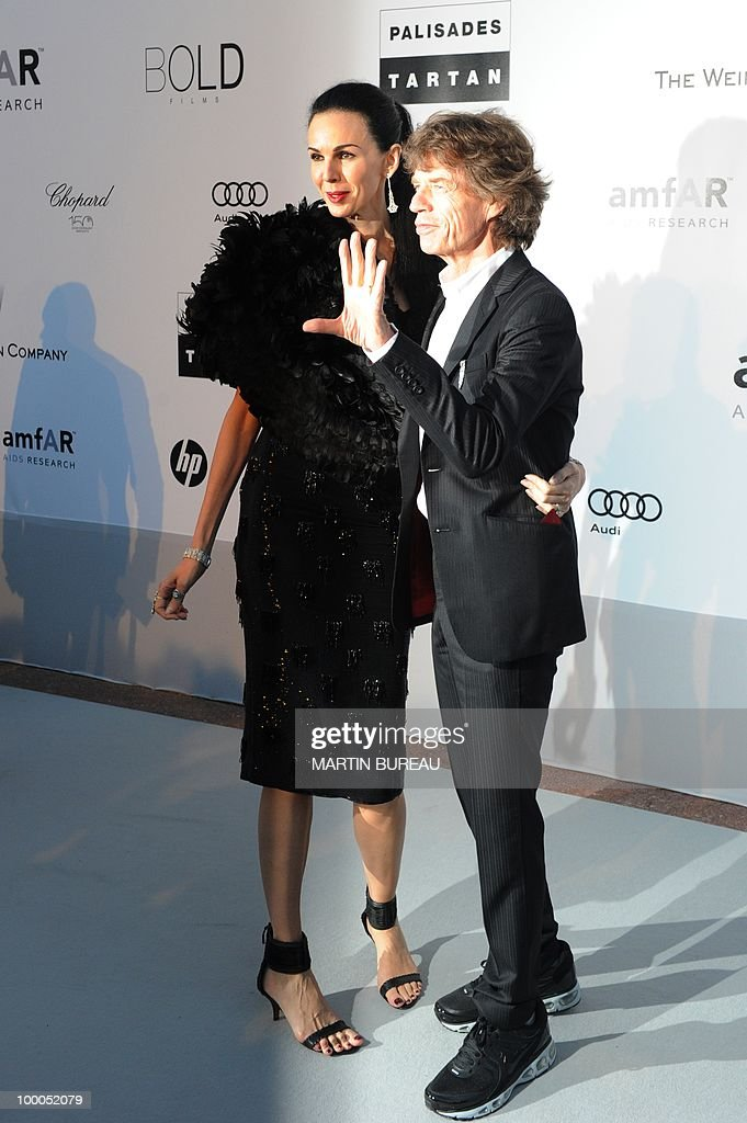 English singer Mick Jagger and American designer L'Wren Scott pose while arriving to attend the 2010 amfAR's Cinema Against Aids on May 20, 2010 in Antibes, southeastern France.