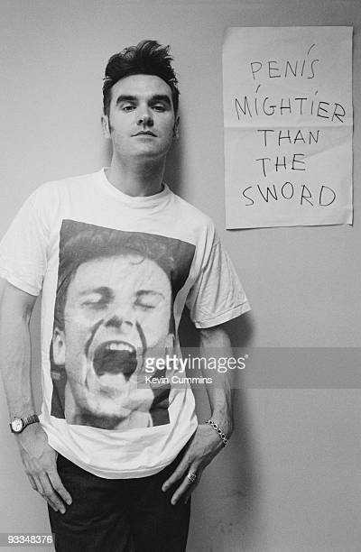 English singer Morrissey standing in front of a sign reading 'Penis Mightier Than The Sword' during the Japanese leg of his 'Kill Uncle Tour' 5th...