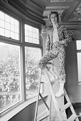English singer musician and actor David Bowie paints the coving of his ground floor flat at Haddon Hall in silver paint Beckenham southeast London...